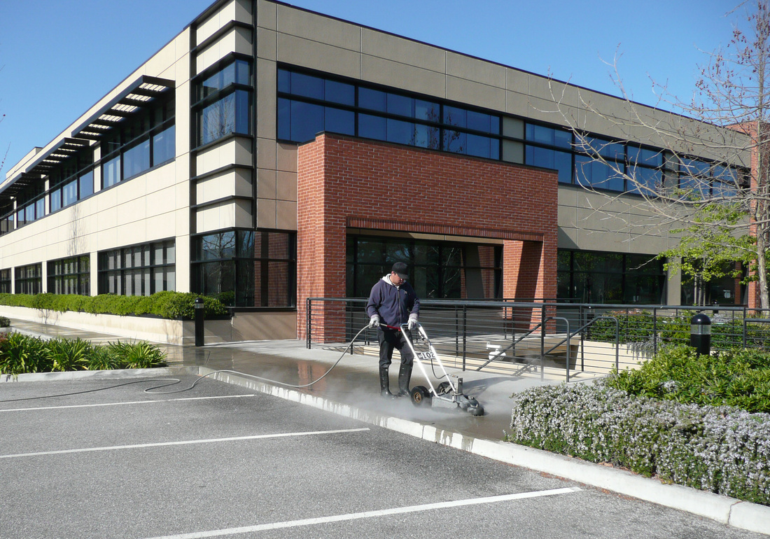 Tony Addy crew member pressure washing outside office buildings